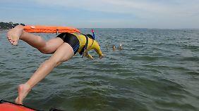 Ein Rettungsschwimmer springt vom Boot ins Wasser, um Badende zu bergen.