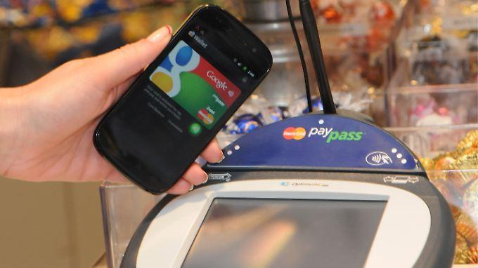 Ein Smartphone wird an einer Supermarkt-Kasse neben ein so genanntes PayPass Gerät zur elektronischen Zahlungsabwicklung gehalten.