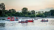 Rettungskräfte in Booten suchen auf dem Rhein bei Biebesheim (Hessen) nach einem Urlauber, der seinen Sohn aus dem Wasser retten wollte.
