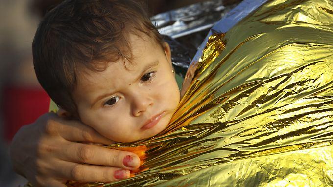 Eine Mutter hüllt ihr Kind nach der Ankunft auf der griechischen Insel Kos in eine Rettungsdecke. Auf der kleinen Insel sind in diesem Jahr bereits 124.000 Flüchtlinge angekommen