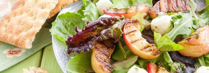 Eine gesunde Mischung aus grünen Salaten, gebratenen Pfirsichen und Mozzarella.