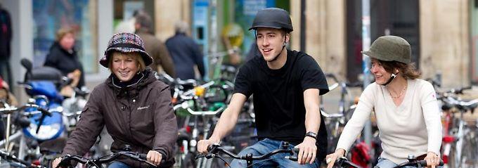 Ob lässiger Schlapphut, coole Schirmmütze oder ein Hut im Sherlock-Holmes-Stil: Fahrradhelme, die mit modernen Mützen und Hüten überzogen werden, sind der neueste Modegag.