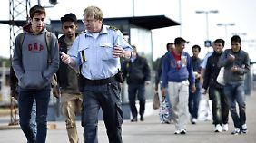 Syrische Flüchtlinge sprechen bei ihrer Ankunft im süddänischen Rodby mit einem Polizisten.