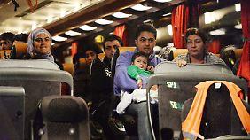 Flüchtlinge vor dem Hauptbahnhof in München. Sie warten darauf, in eine Aufnahmeeinrichtung gebracht zu werden.