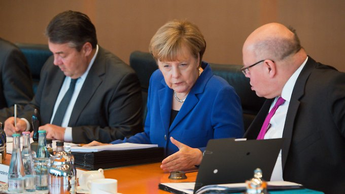 Altmaier und Merkel unterhalten sich zu Beginn der Sitzung des Bundeskabinetts. Wirtschaftsminister Gabriel sitzt daneben.