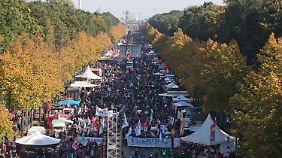 Mehrere tausend TTIP-Gegner ziehen mit Plakaten und Mottowagen durch Berlin.