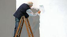 Ein älterer Mann tüncht eine Wand auf der Leipziger Messe.