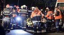 Nach der Explosion in einem Bukarester Nachtklub versorgen Feuerwehrleute Überlebende des Unglücks.