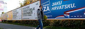 Ein Mann vor einem Wahlplakat der konservativen kroatischen HDZ. Am Sonntag wird ein neues Parlament gewählt.
