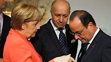 Angela Merkel (l.) muss sich auf Malta vor Francois Hollande (r.) und Frankreichs Außenminster Laurent Fabius erklären.