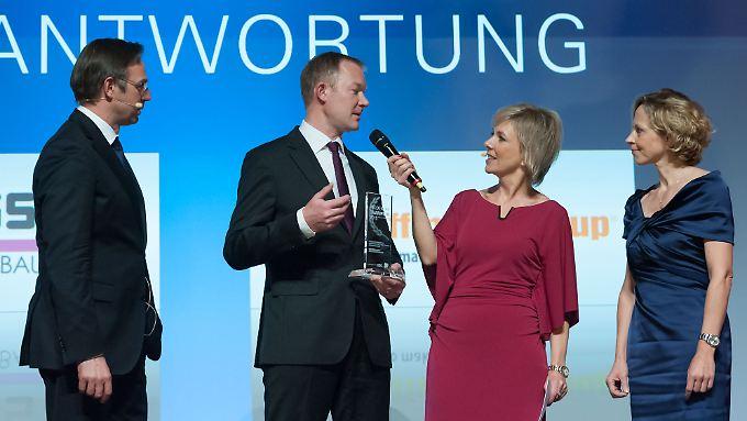 """So sehen Sieger aus: Arne Langer (2. v. li.) und Jutta Wenzl (re.) von Hoffmann GmbH Qualitätswerkzeuge nehmen die Trophäe für den """"Hidden Champion 2015"""" entgegen."""