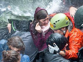 Die Polizei geht mit Wasserwerfern gegen friedliche Gegner des Bahnprojekts vor.