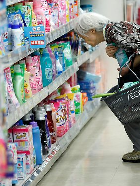 Eine ältere Frau kauft in einem Geschäft in Tokio ein.