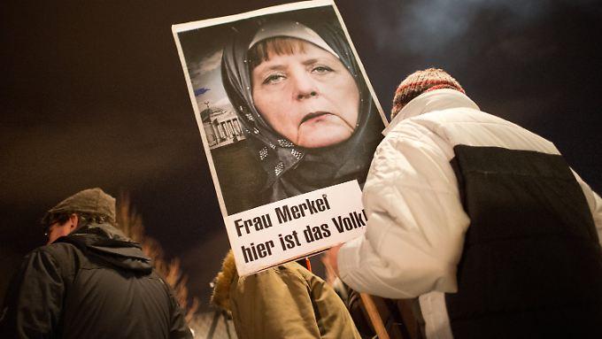 """Angela Merkel mit Kopftuch: Pegida wirft der Bundeskanzlerin immer wieder vor, den """"Willen des Volkes"""" zu ignorieren."""