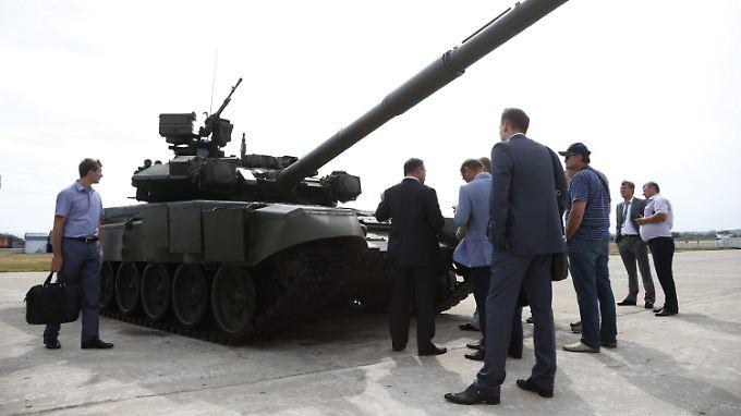 Russischer Panzer und Interessenten auf einer Waffenausstellung.