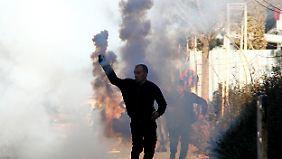 Einer der Demonstranten wirft einen Tränengas-Kanister zurück auf Polizisten.