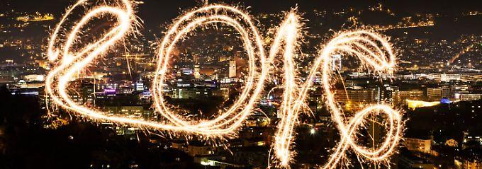 """Mit Hilfe einer Langzeitbelichtung wird in Stuttgart der mit einer Wunderkerze in die Luft geschriebene Schriftzug """"2016"""" lesbar. Foto: Christoph Schmidt/dpa"""