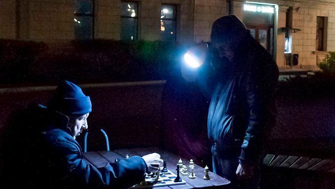 Mit einer Taschenlampe behelfen sich diese beiden Schachspieler in Sewastopol auf der Krim.