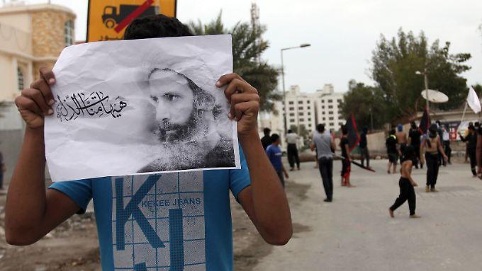 Ein Demonstrant hält ein Bild von Nimr al-Nimr in den Händen.