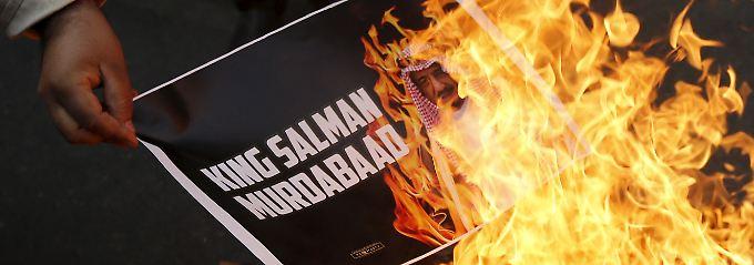 Schiitische Demonstranten verbrennen ein Bild des saudischen Königs bei einer Protestveranstaltung im indischen Neu-Delhi.