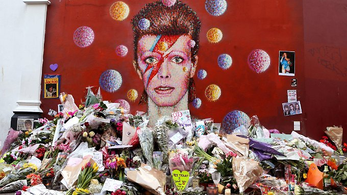 Vor dem Wandgemälde von David Bowie in Brixton stapeln sich die Blumen.