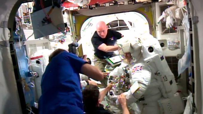 Nach fünf Stunden Außeneinsatz schälten die Kollegen Astronaut Peake wieder aus dem Anzug - etwas früher als geplant.