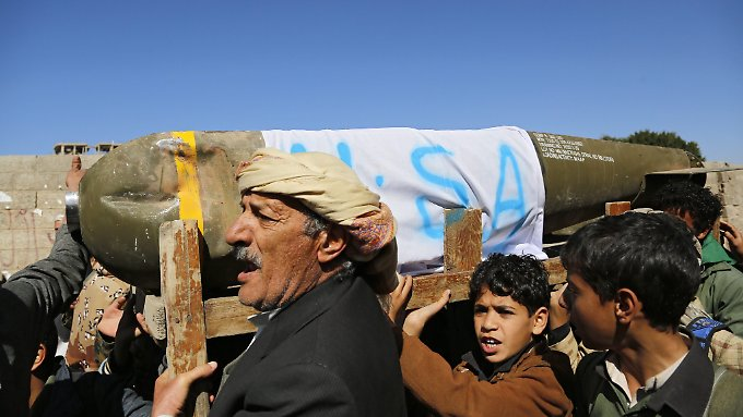 Jemeniten, die eine mutmaßliche Streubombe US-amerikanischer Produktion tragen und Anti-saudische Parolen rufen.