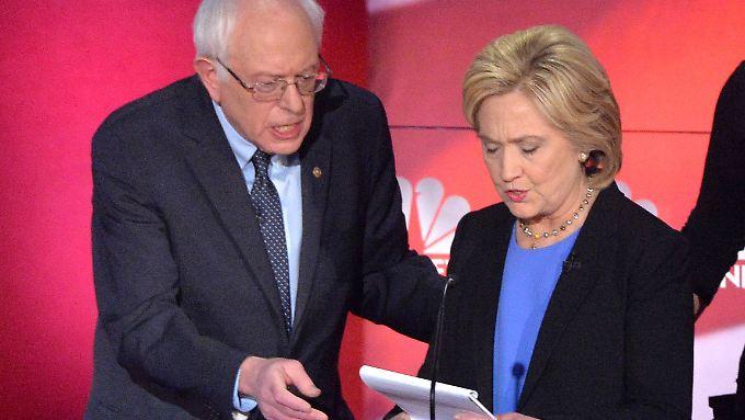 In einer Werbepause gehen Bernie Sanders und Hillary Clinton noch ein paar Papiere durch.
