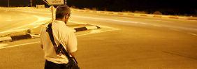 Ein bewaffneter Siedler kontrolliert nach dem Attentat auf eine Frau eine Straße nahe der Siedlung Otniel.