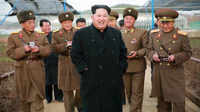 Nordkoreas Machthaber Kim Jong Un umgeben von Militärs, die eifrig Notizen machen.