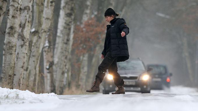 Regen auf gefrorenem Boden ergibt vereiste Straßen, die gefährlich für Fußgänger und Autos sind.