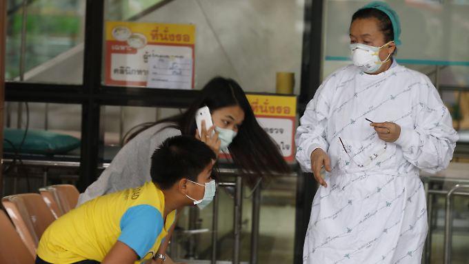 Krankenschwester und Besucher im Bamrasnaradura Infectious Disease Institute tragen Schutzmasken.