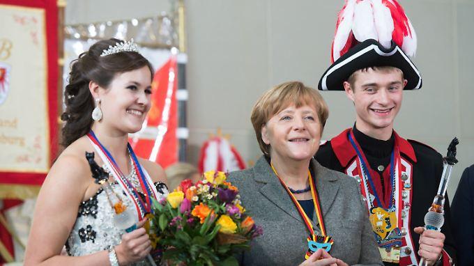 Am Dienstag erhielt Angela Merkel nicht nur Post aus München, sondern auch mehrere Karnevalsorden. Hier die Kanzlerin mit Prinzessin Sophia I. von Chirurgien und Prinz Johannes II. von Technologien aus Bayern.