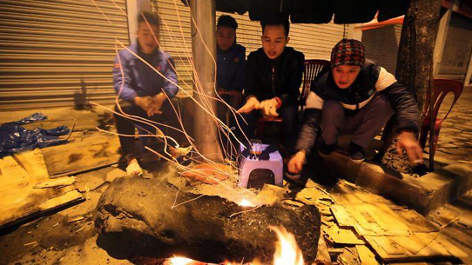 Diese Vietnamesen schützen sich am offenen Feuer vor den ungewohnten Temperaturen.