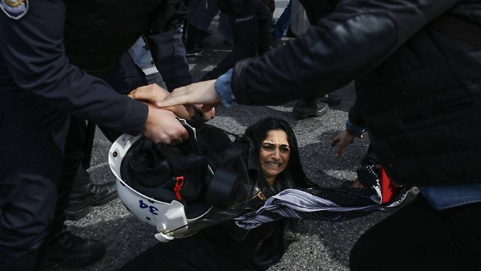 Eine verletzte Frau wird von Polizisten umringt.