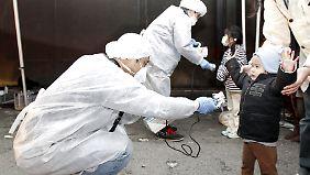 Japanische Ärzte prüfen im März 2011 die Strahlenbelastung von Kindern.