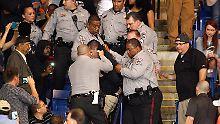 Sicherheitskräfte führen den Demonstranten ab: Kurz nach dieser Aufnahme wurde der 26-Jährige ins Gesicht geschlagen.