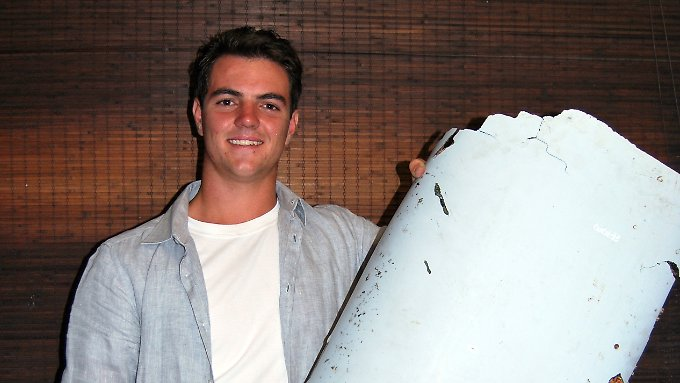 Finder Liam Lotter posiert mit einem weiteren mutmaßlichen Bruchstück des verschollenen Flugzeugs von Flug MH370.