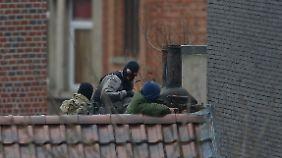 Polizisten nehmen im Brüsseler Stadtteil Forest die Wohnung der drei Angreifer ins Visier.