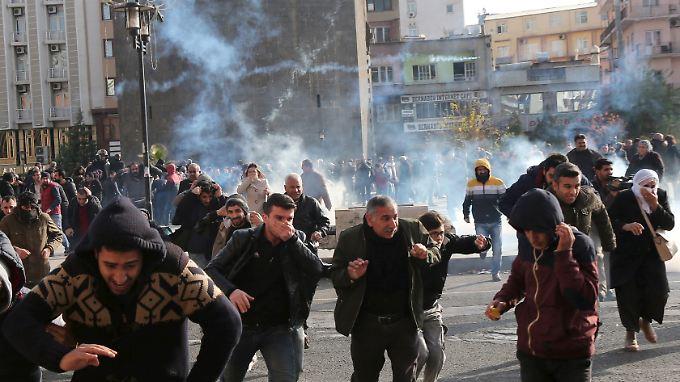Türkische Polizisten lösen eine Demonstration gegen die Ausgangssperre in Sur mit Tränengas auf.