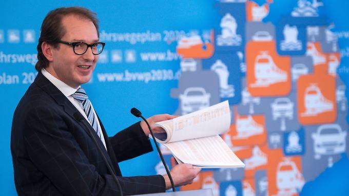 """Das Schriftstück in Dobrindts Hand nennt sich """"Bundesverkehrswegeplan"""" und enthält Infrastrukturprojekte bis 2030."""