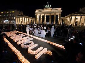 """Aktivisten des WWF vor dem Brandenburger Tor in Berlin anlässlich der """"Earth Hour"""" 2016."""