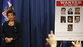 Die US-Generalstaatsanwältin Loretta Lynch stellt die Anklageschrift vor - rechts die gesuchten mutmaßlichen Hacker.