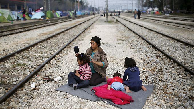 Diese Mutter blockiert mit ihren Kindern die Bahngleise am Grenzübergang Idomeni. Sie gehört zu den vielen Flüchtlingen, die noch Hoffnung haben, dass der Grenzübergang geöffnet wird.