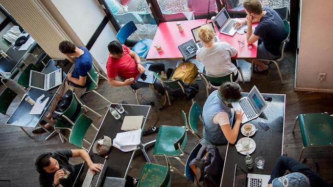 Kaffee und WLAN:Gäste des Café St. Oberholz in Berlin-Mitte sitzen vor ihren Notebooks.