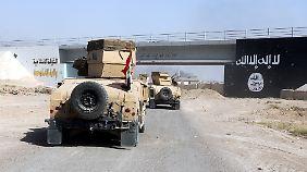 Irakische Regierungstruppen passieren in Falludscha eine Brücke mit der Flagge des Islamischen Staates.