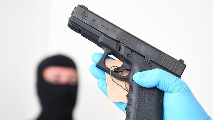 Beamte des Zollfahndungsamtes präsentieren eine der Waffen, die bei dem 31-Jährigen beschlagnahmt wurden.