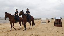 Sehen und gesehen werden: Die Urlaubspolizei reitet durchs Watt