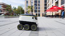 Ein Lieferroboter des Unternehmens Starship Technologies fährt durch ein Düsseldorfer Wohngebiet.