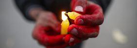 Ein Kind zündet in einem Heim für HIV-infizierte Jugendliche in Nepal am Welt-Aids-Tag eine Kerze an.